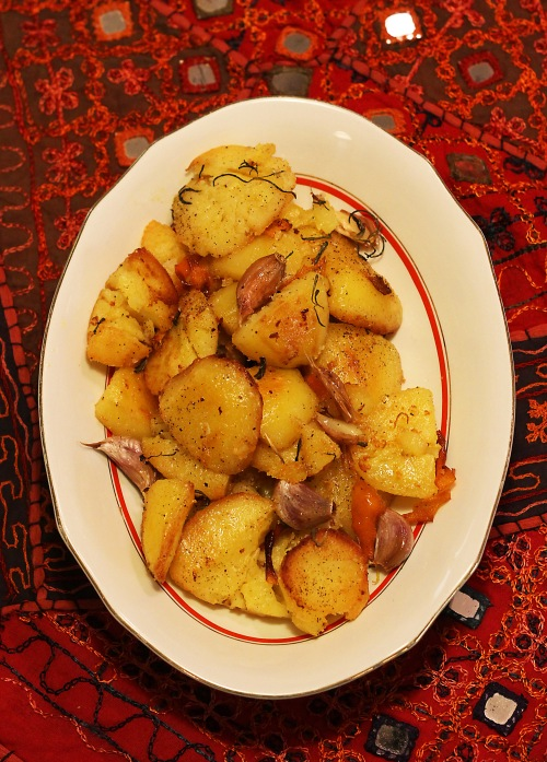 Rapeakuorisiksi paistuneet perunat valkosipulin, appelsiininkuoren ja rosmariinin kanssa.