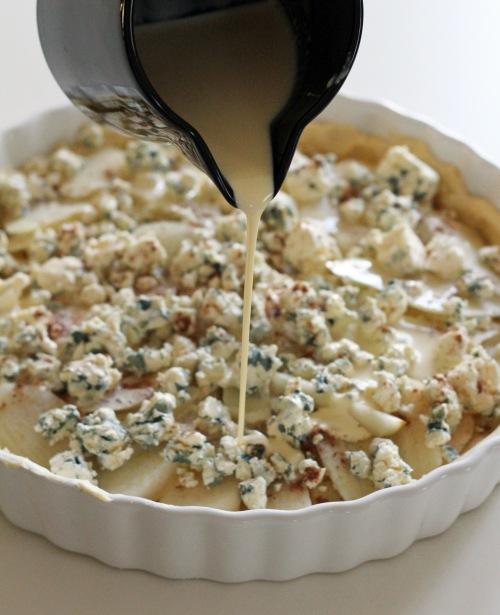 Lado vuokaan ensin päärynät, sitten murennettu juusto ja kaada viimeseksi päälle kerma, johon olet sekoittanut kananmunan.