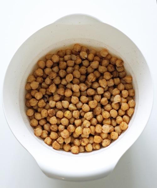 Pyörittele kypsiä kikherneitä kulhossa niin, että ne ovat kauttaaltaa mausteiden peitossa.